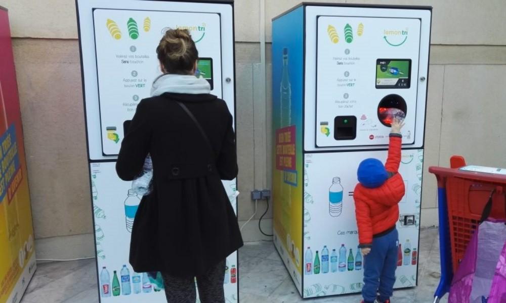 Une maman et son enfant dépose les bouteilles consignées dans les machines à consigne.