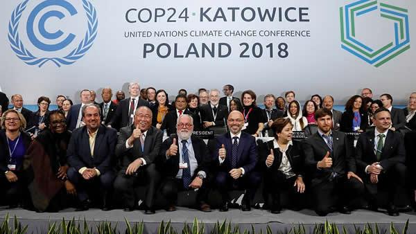 Photo finish de la COP24. Les participants sont très heureux et ils lèvent le pouce.